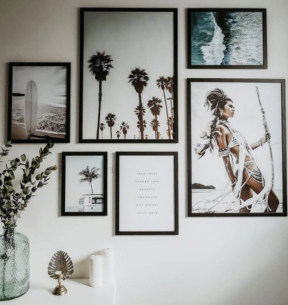 Gallery wall with summery posters in black frames